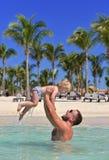 Het jonge geitje van het de babymeisje van de papaholding in handen tropische overzeese strandvakantie stock fotografie