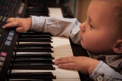 Het jonge geitje van het jongenskind het spelen op de digitale synthesizer van de toetsenbordpiano Royalty-vrije Stock Foto