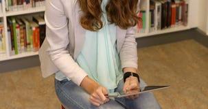 Het jonge geitje van het leraarsonderwijs op digitale tablet in bibliotheek stock videobeelden