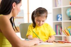 Het jonge geitje van het vrouwenonderwijs om te schrijven Het elementaire leerling schilderen met leraar stock fotografie