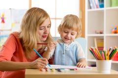 Het jonge geitje van het vrouwenonderwijs om te schrijven Het elementaire leerling schilderen met leraar royalty-vrije stock afbeeldingen