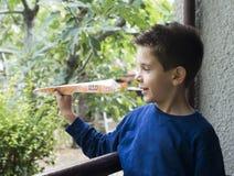 Het jonge geitje werpt document vliegtuig Stock Foto's
