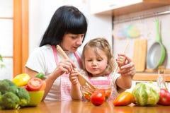 Het jonge geitjedochter die van het moederonderwijs salade mengen bij keuken stock afbeelding