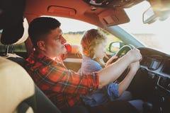 Het jonge geitjedochter van het vaderonderwijs om een auto, familie het reizen te drijven stock afbeeldingen