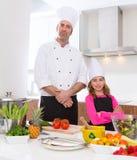 Het jonge geitjemeisje van de chef-kok hoofd en ondergeschikt leerling bij het koken van school Royalty-vrije Stock Afbeelding