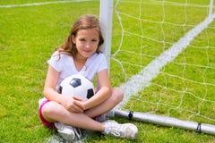 Het jonge geitjemeisje van de voetbalvoetbal op gras met bal wordt ontspannen die Royalty-vrije Stock Foto's