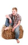 Het jonge geitjezitting van de landbouwer op hooi Royalty-vrije Stock Fotografie