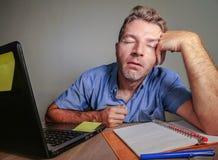 Het jonge gekke beklemtoonde en overweldigde mens werken slordig bij bureau wanhopig met laptop computergevoel putte en frustra u stock foto's