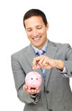 Het jonge geld van de zakenmanbesparing in een piggy-bank royalty-vrije stock fotografie