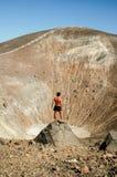 Het jonge gelooide mannelijke model stellen voor een vulkaankrater Royalty-vrije Stock Afbeelding