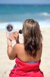 Het jonge gelooide vrouw zetten maakt omhoog terwijl op het strand stock foto