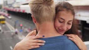 Het jonge gelukkige bekoorde meisje koestert zacht haar vriend bij stedelijke straat stock video