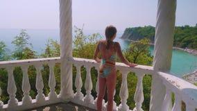 Het jonge gelukkige Kaukasische meisje lanceert aan het traliewerk en bekijkt neer het overzeese strand stock video
