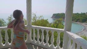 Het jonge gelukkige Kaukasische meisje lanceert aan het traliewerk en bekijkt neer het overzeese strand Slowmo stock videobeelden