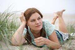 Het jonge gelukkige meisje ontspannen op zandduinen van het strand van St.Peter royalty-vrije stock fotografie