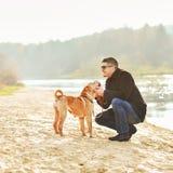 Het jonge gelukkige mens spelen met zijn hond Royalty-vrije Stock Afbeeldingen