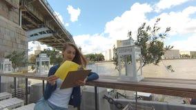 Het jonge gelukkige menu van de vrouwenlezing in straatkoffie stock video
