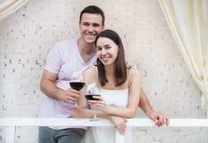 Het paar van ?appy genieten van glazen rode wijn binnen Stock Afbeeldingen
