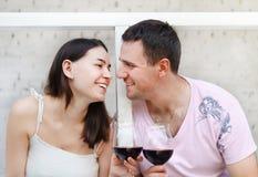 Het jonge gelukkige paar genieten van glazen rode wijn Royalty-vrije Stock Afbeeldingen