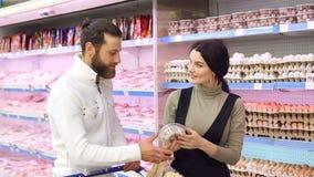 Het jonge gelukkige paar kiest kwartelseieren in supermarkt Langzame Motie Portret stock footage