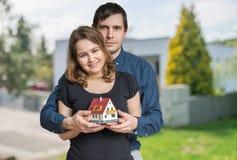 Het jonge gelukkige paar in liefde droomt en plant een nieuw huis Stock Foto's