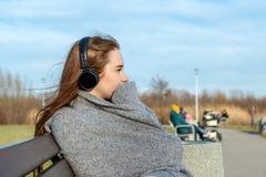 Het jonge, gelukkige roodharigemeisje in de lente in het park dichtbij de rivier luistert aan muziek door draadloze bluetoothhoof royalty-vrije stock foto