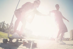 Het jonge gelukkige vrienden het schaatsen longboarding in een stadspark royalty-vrije stock afbeelding