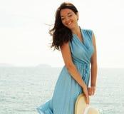 Het jonge gelukkige vrouw stellen dichtbij overzees royalty-vrije stock foto