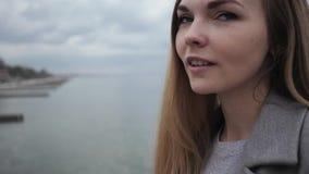 Het jonge gelukkige vrouwenblonde met lang haar in een grijze laag en jeans loopt langs de overzeese promenade stock video