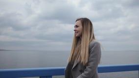 Het jonge gelukkige vrouwenblonde met lang haar in een grijze laag en jeans loopt langs de overzeese promenade stock footage