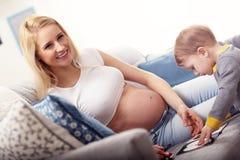 Het jonge Gelukkige Zwangere vrouw spelen met zoon royalty-vrije stock afbeeldingen