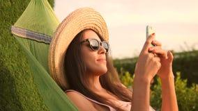 Het jonge Gemengde Meisje van de Rastoerist in Zonnebril en Straw Hat Using Mobile Phone in Hangmat in Park bij Natuurlijke Zonso stock video