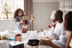 Het jonge gemengde rasmeisje die giften geven aan haar ouders op Kerstmisochtend, ouders die omhoog in bed zitten, sluit omhoog royalty-vrije stock foto's
