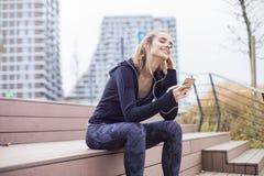 Het jonge geschikte sportieve vrouw rusten en luistert muziek op mobiele telefoon stock foto