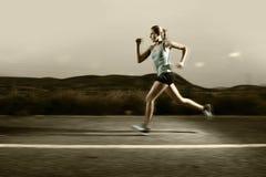 Het jonge geschikte sportvrouw lopen in openlucht op asfaltweg in berglandschap en het dramatische licht plaatsen voor reclame Stock Fotografie