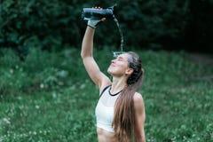 Het jonge geschiktheidsmeisje die koud water op gezicht gieten na stoot, sluit omhoog horizontaal gezichtsschot aan Vrouw in bos  royalty-vrije stock afbeeldingen