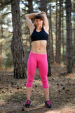 Het jonge Geschiktheidsvrouw Uitrekken zich in de Pijnboom Forest Female Runner Doing Stretches Gezond levensstijlconcept Stock Foto's