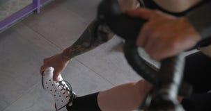 Het jonge getatoeeerde fietservrouw cirkelen met fiets thuis fitness sporttraining benen het uitrekken zich Binnenlandse woonkame stock footage