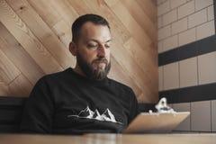 Het jonge getatoeeerde menu van de mensenholding bij koffie royalty-vrije stock afbeeldingen