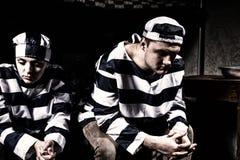 Het jonge gevangenepaar die eenvormige gevangenis dragen heeft binnen niettemin verloren Royalty-vrije Stock Fotografie
