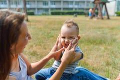 Het jonge gezicht van de moederzitting aan haar het leuke peuterzoon speel slaan dient park, het concept van de levensstijlpret i Stock Afbeeldingen