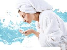 Het jonge gezicht van de vrouwenwas met schoon water stock afbeeldingen