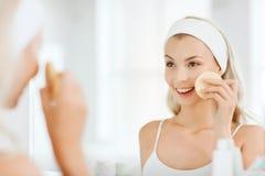 Het jonge gezicht van de vrouwenwas met spons bij badkamers stock foto's