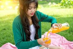 Het jonge glas van de vrouwenholding, het drinken jus d'orange met vruchten mand stock fotografie