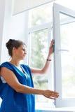 Het jonge glas van het Vrouwen schoonmakende venster Schoonmakende Bedrijfarbeider Stock Fotografie