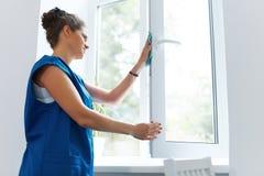 Het jonge glas van het Vrouwen schoonmakende venster Schoonmakende Bedrijfarbeider Stock Afbeeldingen