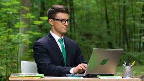 Het jonge het glimlachen beambte typen op laptop zitting in groen park, langzaam-mo stock videobeelden