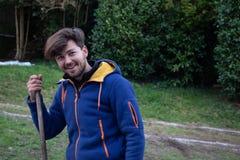 Het jonge glimlachen in het landelijke plaatsen, die een houten stok houden stock foto's