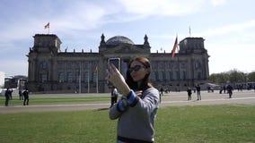Het jonge het Glimlachen Zelfportret van Vrouwenselfie op Smartphone Reichstag die Berlijn bouwen stock videobeelden