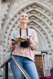 Het jonge glimlachende meisje doorbladert het boekje Royalty-vrije Stock Fotografie